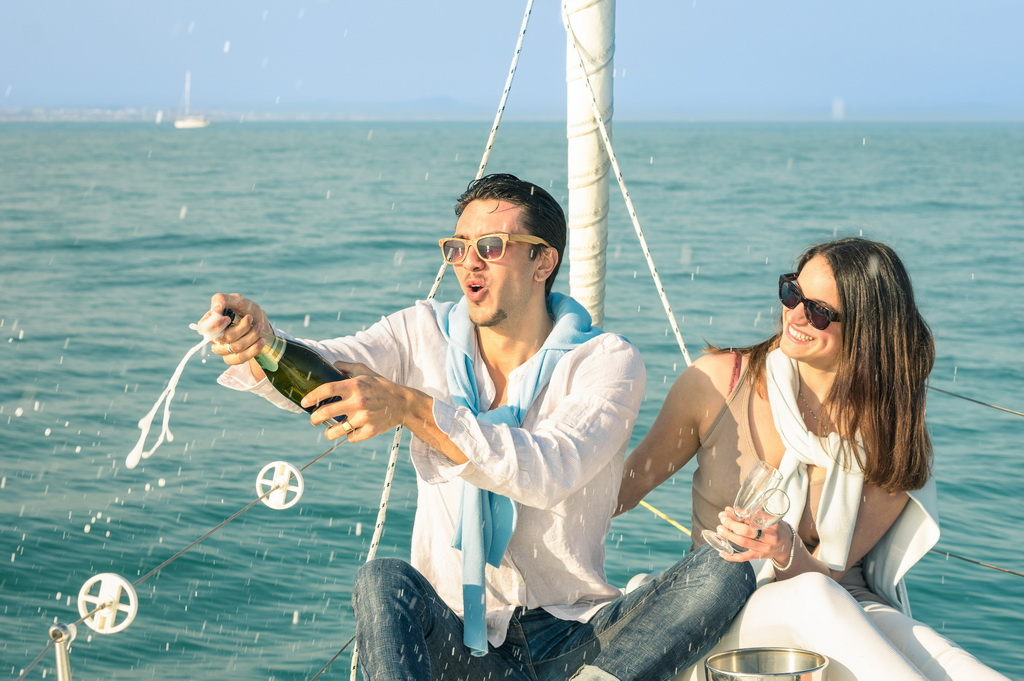 Young Couple In Love On Sailing Boat Cheering With Champagne Win